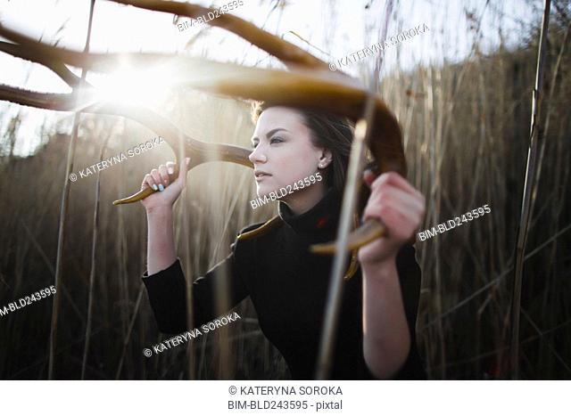 Caucasian woman holding antlers around head