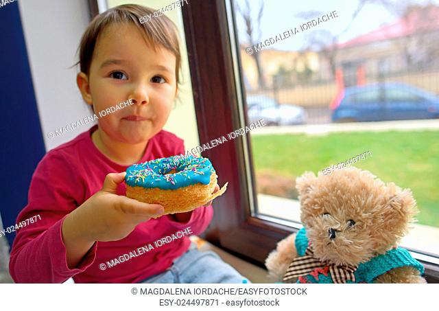 little girl eating donuts with her toy friend
