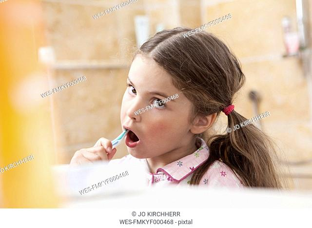 Germany, North Rhine Westphalia, Cologne, Girl brushing teeth in bathroom