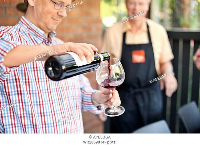 Midsection of man pouring red wine in glass with friend in background at porch