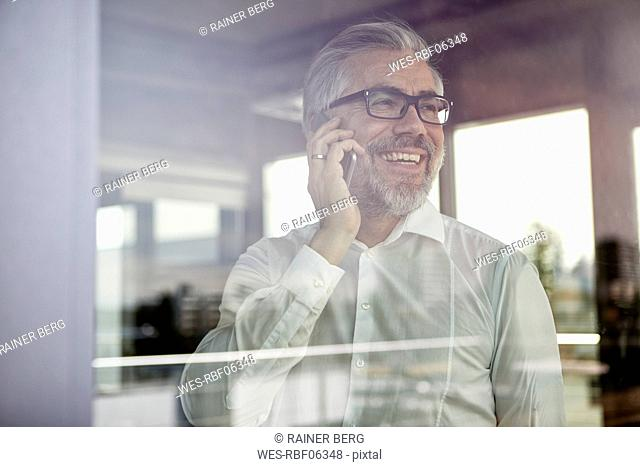 Laughing businessman at the window talking on cell phone