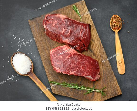 two raw pieces of classic beef steak lie on a wooden board, black table, top view