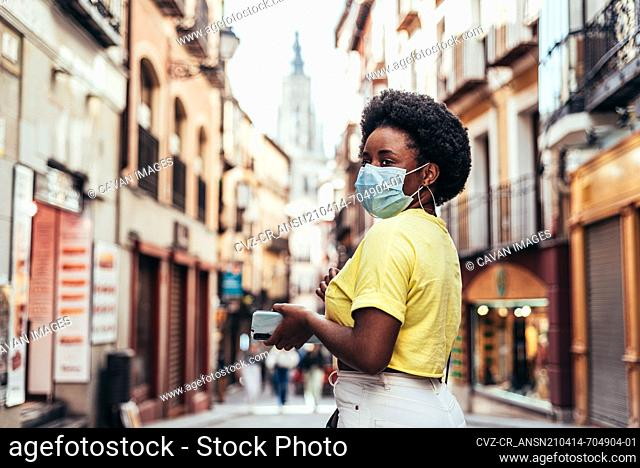 Portrait of black girl with face mask, afro hair and hoop earrings walking down a central street of the old city