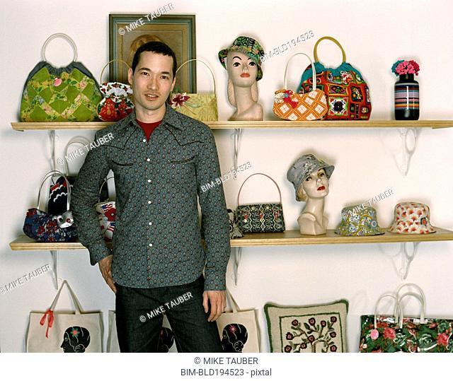 Mixed race man standing in retro purse shop