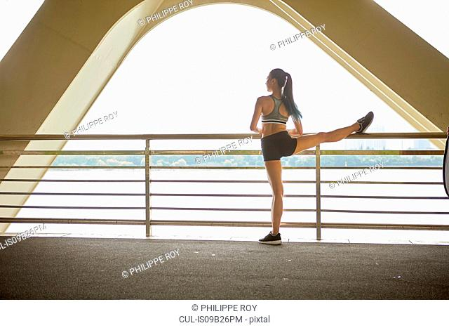 Rear view of woman with leg raised on railing stretching