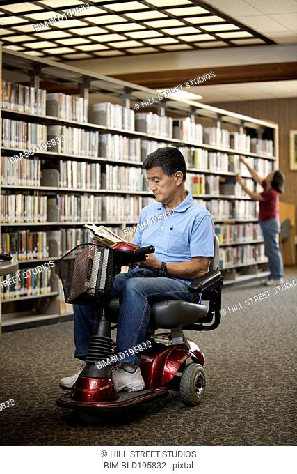 Japanese man in motorized scooter reading book in library