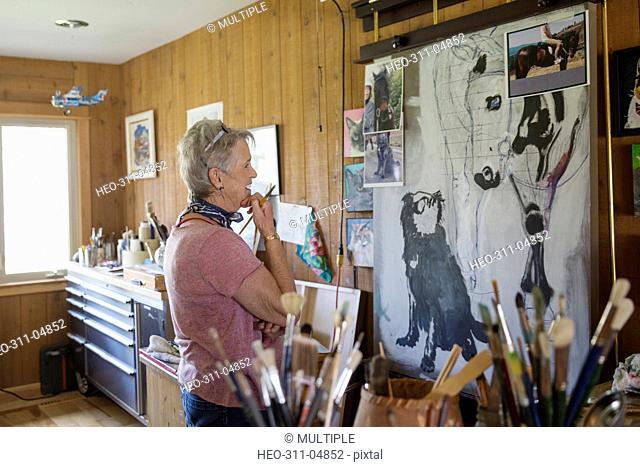 Pensive senior woman artist painting examining paintings in art studio