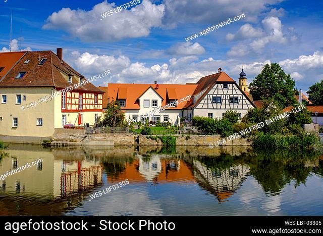 Germany, Bavaria, Wassertrudingen, Wornitzpark watermill reflecting in Wornitz River