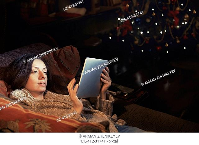 Woman using digital tablet relaxing on sofa in living room near Christmas tree