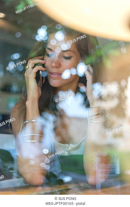 Young woman on cell phone behind windowpane of a cafe