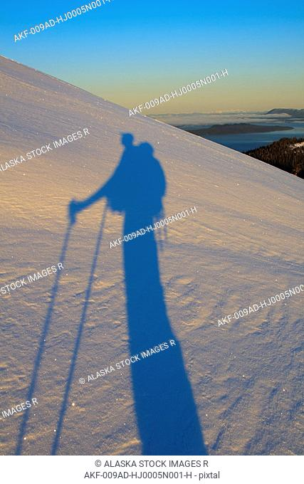 A skier casts a long shadow over the snow at dawn as he ascends a mountain on Wrangell Island, Alaska