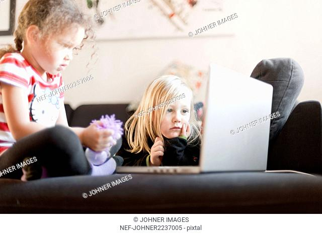 Two girls looking at laptop on sofa