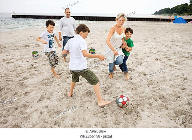 Family enjoying soccer at beach against sky