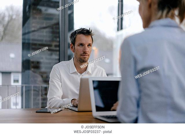 Businessman and woman sitting at desk, working on laptop