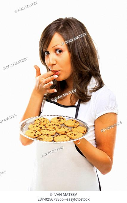 Young woman holding a tray with homemade chocolate cookies, licking her finger and looking at camera