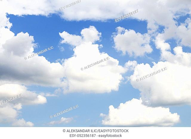 Clear blue sky with White Fluffy clouds as background