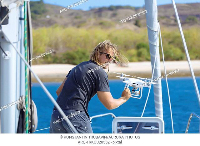 Rear view of man flying drone on yacht