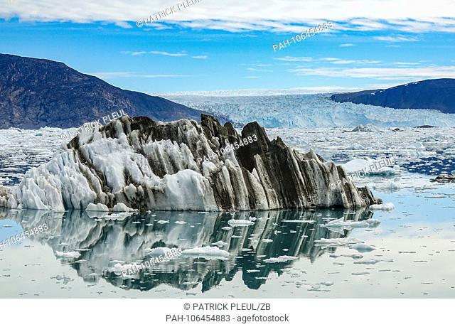26.06.2018, Gronland, Denmark: A dirty iceberg floating in the fjord in front of the Eqi Glacier near the coastal town of Ilulissat in western Greenland