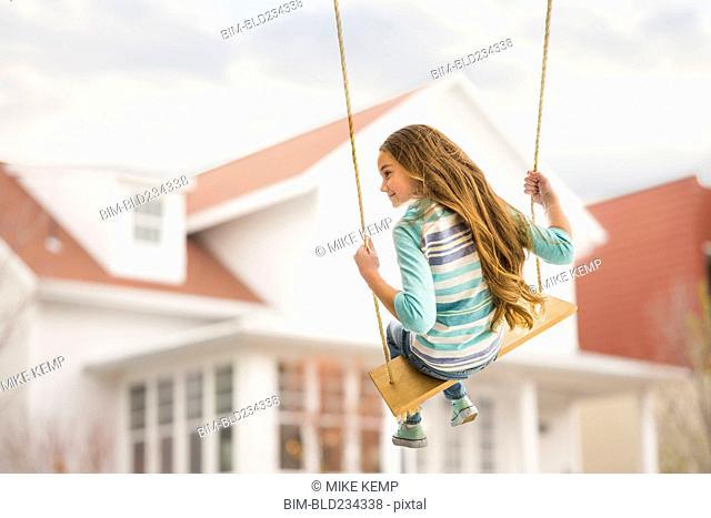 Caucasian girl on rope swing near house
