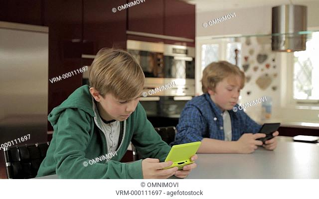 Two Boys Playing Handheld Video Games in Kitchen