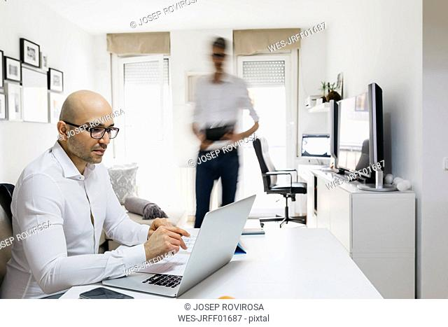 Man using laptop in home office with colleague moving past