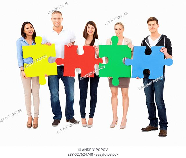 Group Of A People Assembling Jigsaw Puzzle On White Background