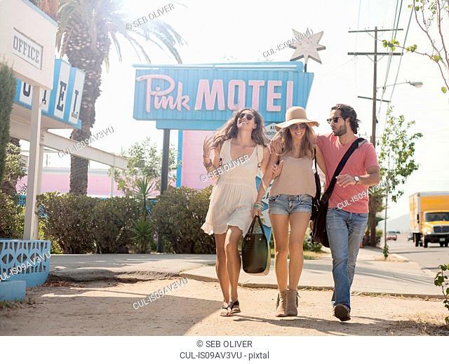 Friends walking past motel, Los Angeles, California, USA