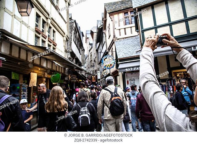 Visitors walk on medieval streets of Mont Saint-Michel, France