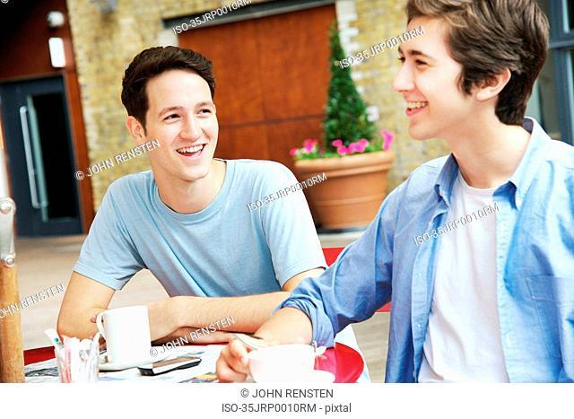 Smiling men having coffee at cafe