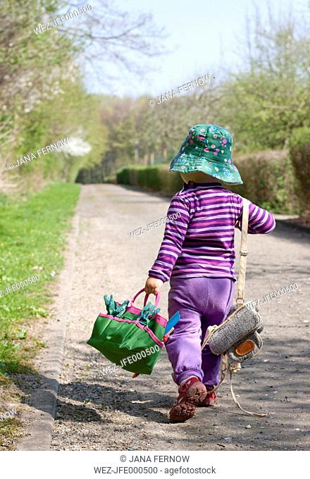 Little girl with hat carrying bags, back view
