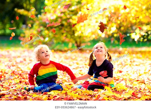 Kids play in autumn park. Children throwing yellow maple leaves. Boy and girl jump and run with oak leaf. Fall foliage. Family outdoor fun in autumn