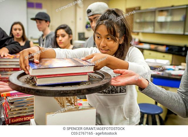 A Hispanic high school student in Mission Viejo, CA, stacks weights on a structural bridge model in a conceptual physics class to determine its breaking point