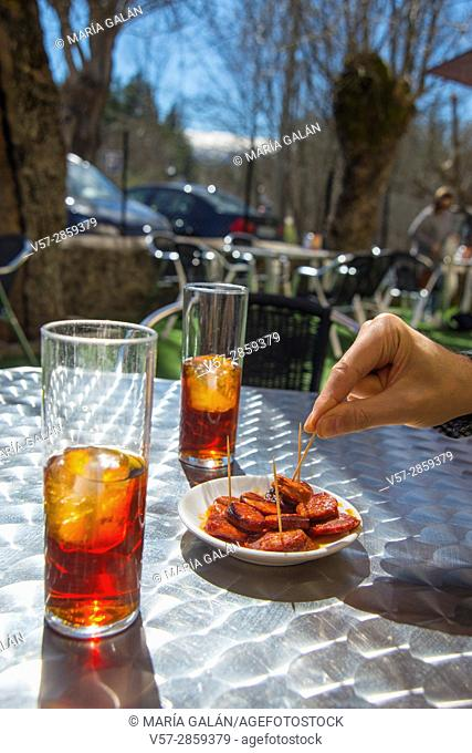Two glasses of vermouth and man's hand having tapa of chorizo in a terrace. Spain