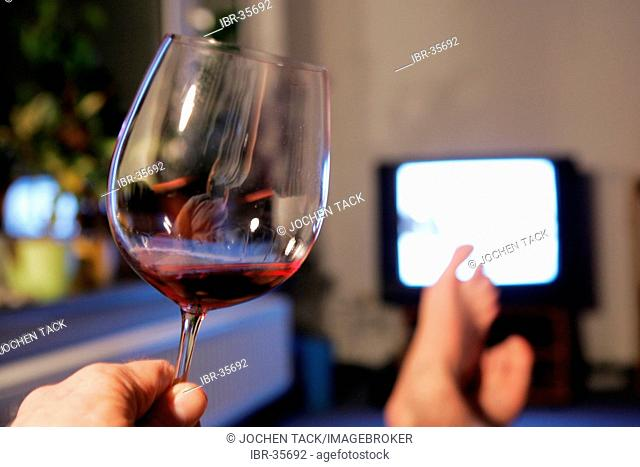 DEU, Germany : man in front of an TV. Glas of red wine