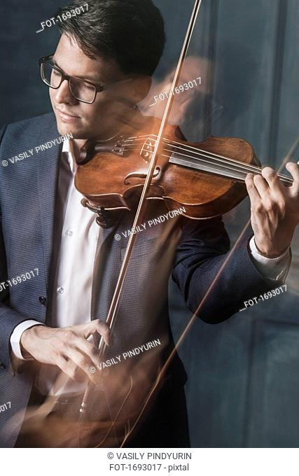 Blurred motion of handsome young man playing violin with closed eyes