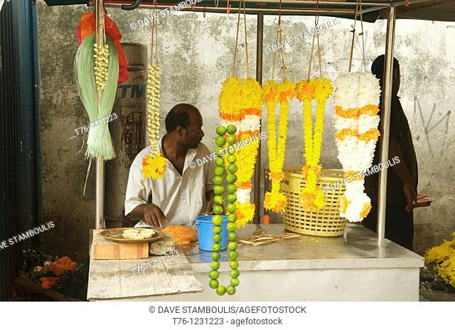 Indian selling flowers for offerings in front of Hindu Temple in Kuala Lumpur, Malaysia