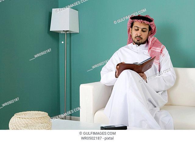 Arab man sitting on sofa, writing