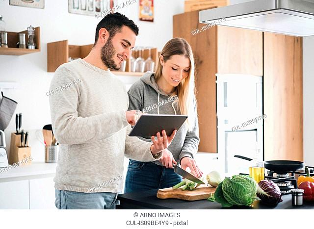Couple preparing food using digital tablet