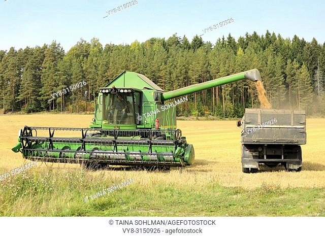 Salo, Finland - September 8, 2018: John Deere combine unloads harvested grain onto truck trailer on a clear day of autumn in South of Finland