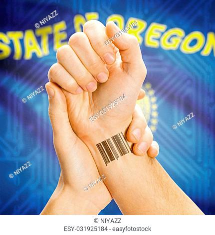Barcode ID number tatoo on wrist and USA statesl flag on background - Oregon