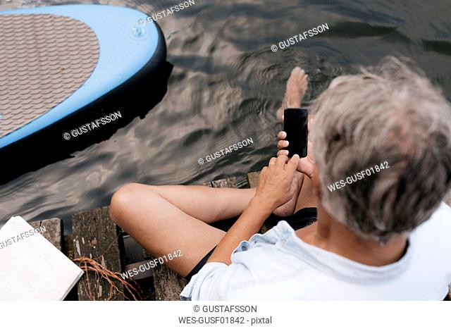 Senior man sitting on jetty at a lake using cell phone
