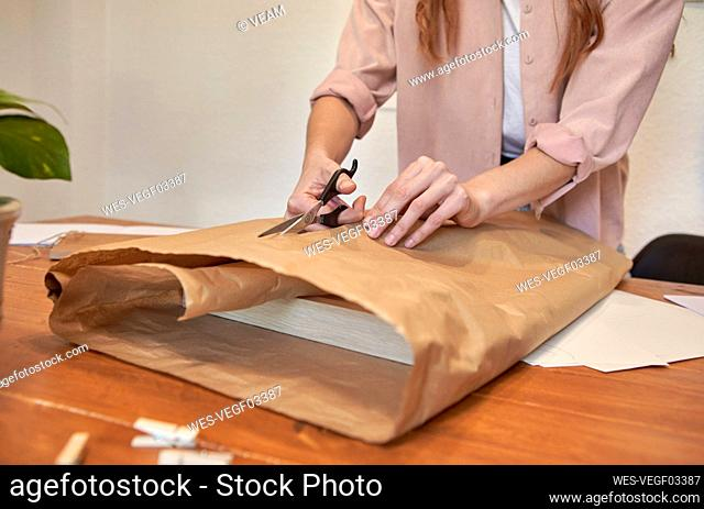 Female artist cutting brown paper while preparing package at desk in living room