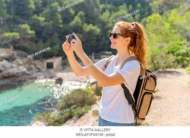 Redheaded woman standing on viewpoint and photographing with her smartphone