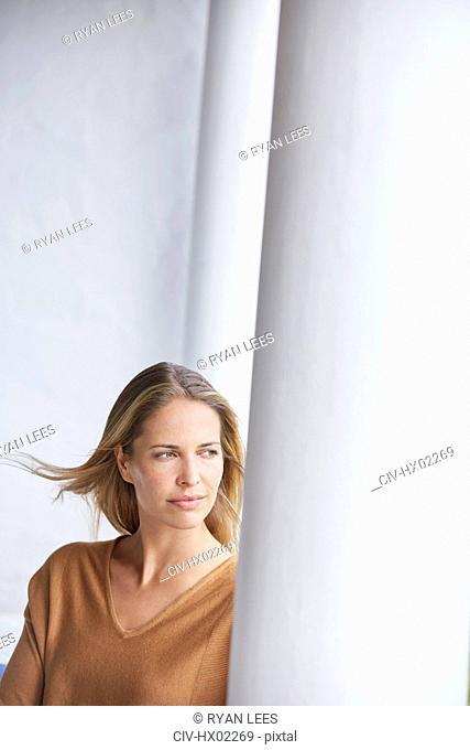 Pensive blonde woman looking away on patio