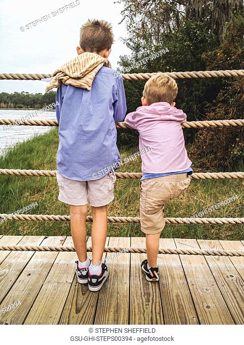 Two Young Boys on Lakeside Dock Peering Through Rope Barrier