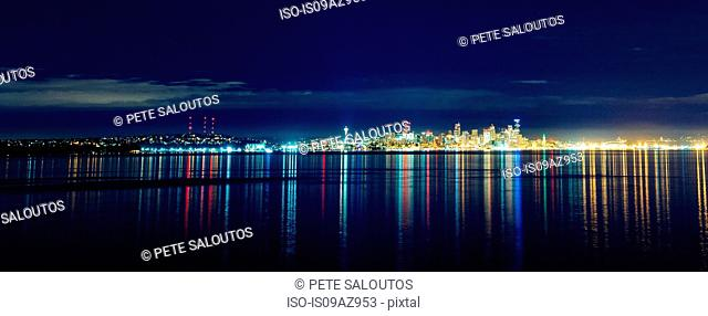 Panoramic view of distant skyline and city lights at night, Seattle, Washington, USA