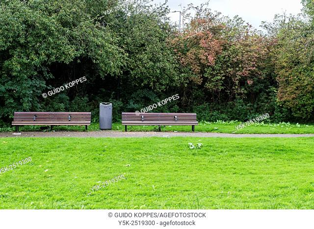 Rotterdam, Netherlands. Two wooden benches and a garbage collector, situated in a small park with meadow and bushes