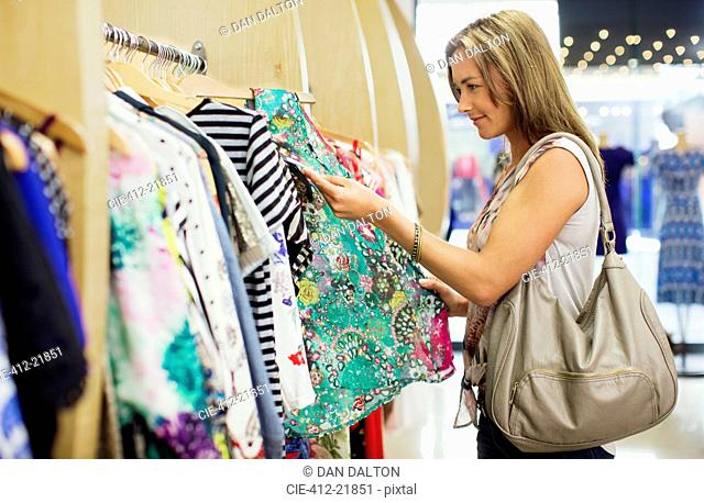 Woman checking price tags while shopping in clothing store
