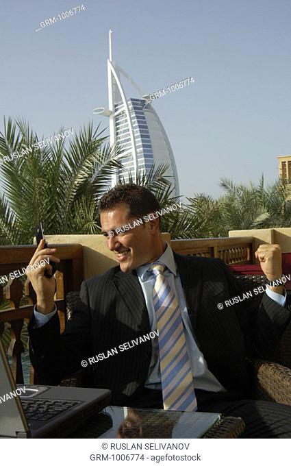 Happy businessman looking at his mobile phone in Dubai (Burj Al Arab hotel in background)