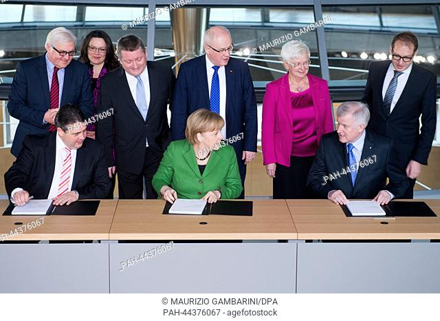German Chancellor Angela Merkel (C), CSU chairman Horst Seehofer (R) and SPD chairman Sigmar Gabriel (L) initial the coalition agreement in the Reichstag in...